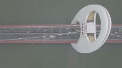 Overhead aerial view of traffic driving over a modern bridge in China Stock Footage