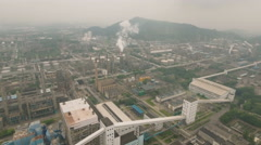 Aerial overview of an oil refinery, heavy industry polluting smokestacks China Stock Footage