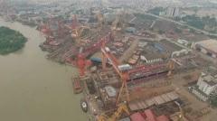 Aerial flight over old and rusty shipyard in China Stock Footage