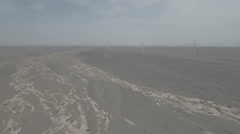 Flying over dry riverbed towards wind energy farm in Chinese deserts Stock Footage