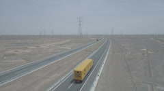 Aerial shot of trucks driving over quiet highway in remote desert China Stock Footage