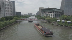 Two cargo vessels sail through modern Hangzhou city center in China Stock Footage