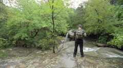 Hiker Stands at Creek at Waterfall in Slow Motion Stock Footage