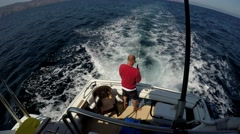 Man fishing behind moving motor yacht in open sea on sunny day. Stock Footage