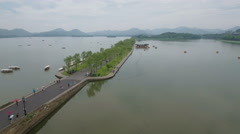 Flying over a promenade at West Lake, a popular tourist attraction in Hangzhou Stock Footage