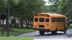 Yellow school bus turning a corner in a neighborhood Stock Footage