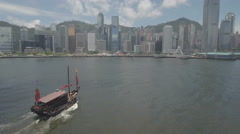 Aerial drone flight traditional wooden junk boat Hong Kong skyline Stock Footage