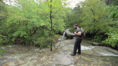Male Hiker Leaves a Creek at Waterfall in Slow Motion Stock Footage