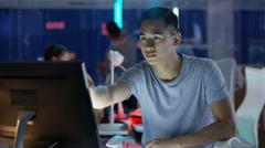 4K Portrait smiling computer game designer working at his desk Stock Footage