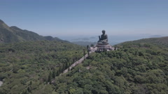 Aerial drone flight bronze Buddha statue in forest Hong Kong Stock Footage