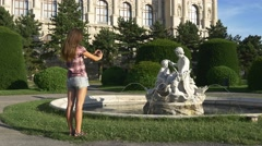 Woman photographs a statue on a mobile phone Stock Footage