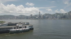 Flying over the Star Ferry Pier in Kowloon to modern skyline of Hong Kong Stock Footage