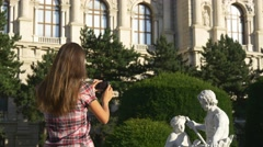 Woman photographs sculpture on the phone Stock Footage