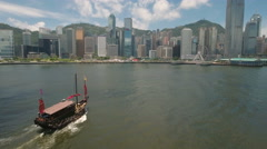 Aerial tracking shot wooden junk boat sailing to modern Hong Kong skyscrapers Stock Footage
