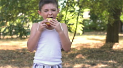 Six-year-old boy eating an apple in the Park Stock Footage