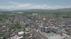Pigeons fly over golden mosque, stunning mountain scenery, Linxia China Stock Footage