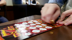 Close up woman scratching lottery ticket called red hot Stock Footage