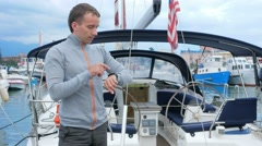 Handsome young man standing near his yacht. He checks messages on the smart Stock Footage