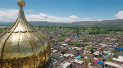 Aerial shot of a beautiful golden mosque in mountain panorama China Asia Stock Footage