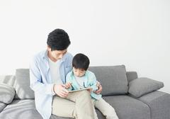 Japanese father and son on the sofa with tablet Stock Photos