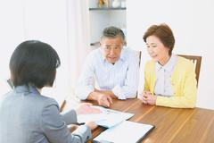 Senior Japanese couple consulting with financial planner Stock Photos