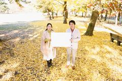 Senior Japanese couple with whiteboard in a city park Stock Photos