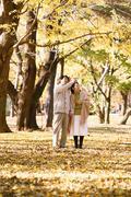 Senior Japanese couple in a city park in Autumn Stock Photos