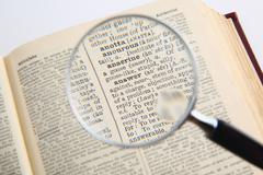 Dictionary and magnifying glass Stock Photos