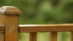 Raindrops fall on to wooden deck railing Stock Footage
