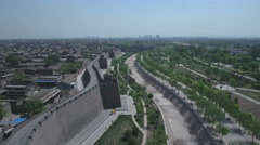 Two people cycle past the high city walls of ancient Pingyao in China Stock Footage