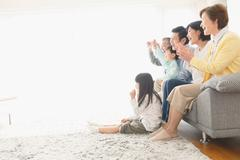 Three-generation Japanese family on the sofa in the living room Stock Photos