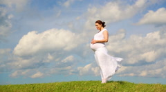 Pregnant woman in field on background of beautiful clouds Stock Footage