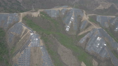 Aerial view of solar panels on mountain slope, renewable energy in China Stock Footage