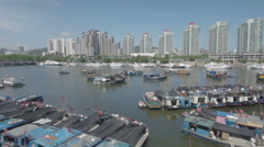 Aerial view of old fishing fleet and modern apartment buildings in Sanya, China Stock Footage