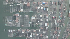 Aerial perspective of network of homes waterways, floating fishing village China Stock Footage
