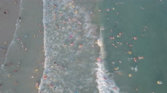 Aerial view crowds of people swimming at busy beach in China Stock Footage