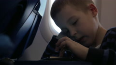 In plane sits a little boy and playing games on the mobile phone Stock Footage