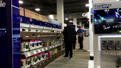 Motion of people buying new digital camera inside Best buy store Stock Footage