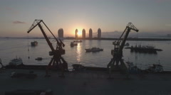 Flying through old rusty cargo cranes in a small port at sunset in Sanya, China Stock Footage