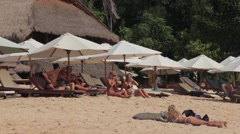 Tourists Relax on the Sun Loungers on the Beach Stock Footage
