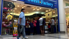 One side of people shopping inside sweet factory store Stock Footage