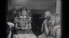 1953: a teen girl in a plaid dress reads a card and opens a gift as her friends Stock Footage