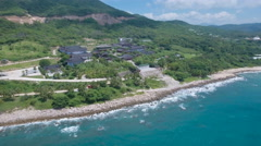 Aerial of beautiful tropical coastline and Buddhist temple complex in China Stock Footage