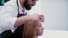 Tylist-hairdresser at work. Man hairdresser makes hair parting Stock Footage