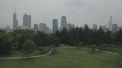 Aerial view of park in Shanghai with city skyline in the background Stock Footage