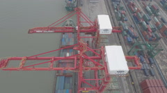 Flying over red cranes loading cargo vessels in the Port of Shanghai Stock Footage