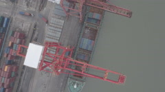 Overhead drone shot loading cargo vessels in container terminal China Stock Footage
