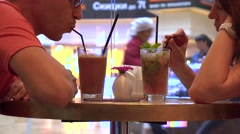Couple having their cold drinks in a shopping mall cafe against big window Stock Footage