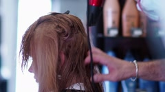 Wet hair is dried by hairdryer. Male hand stylist with a hairdryer Stock Footage