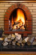 Wood logs and fire in indoor brick fireplace Stock Photos